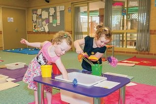 Isla Cockman and Charlize Foley try out the sensory play activities.