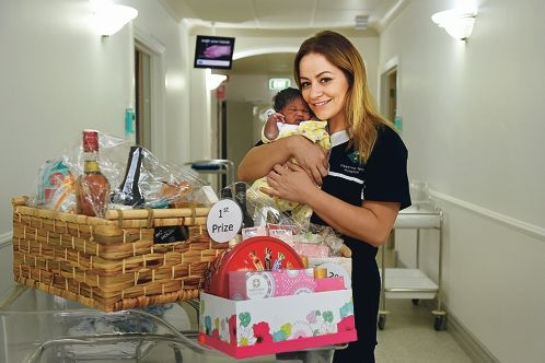 Osborne Park Hospital midwife Ahlem Kassem with newborn baby girl Ayen Pinycileu and raffle hampers.|Picture: Marcus Whisson www.communitypix.com.au d427034