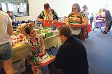 Kaylia Arrigoni and Wayne Belcher (front) with community volunteers helping to pack Christmas boxes for children.