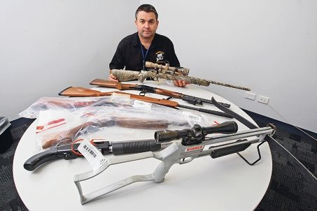 Acting Detective Senior Sergeant Craig Steven with some of the firearms discovered by police. Picture: Bruce Hunt www.communitypix.com.au d426780