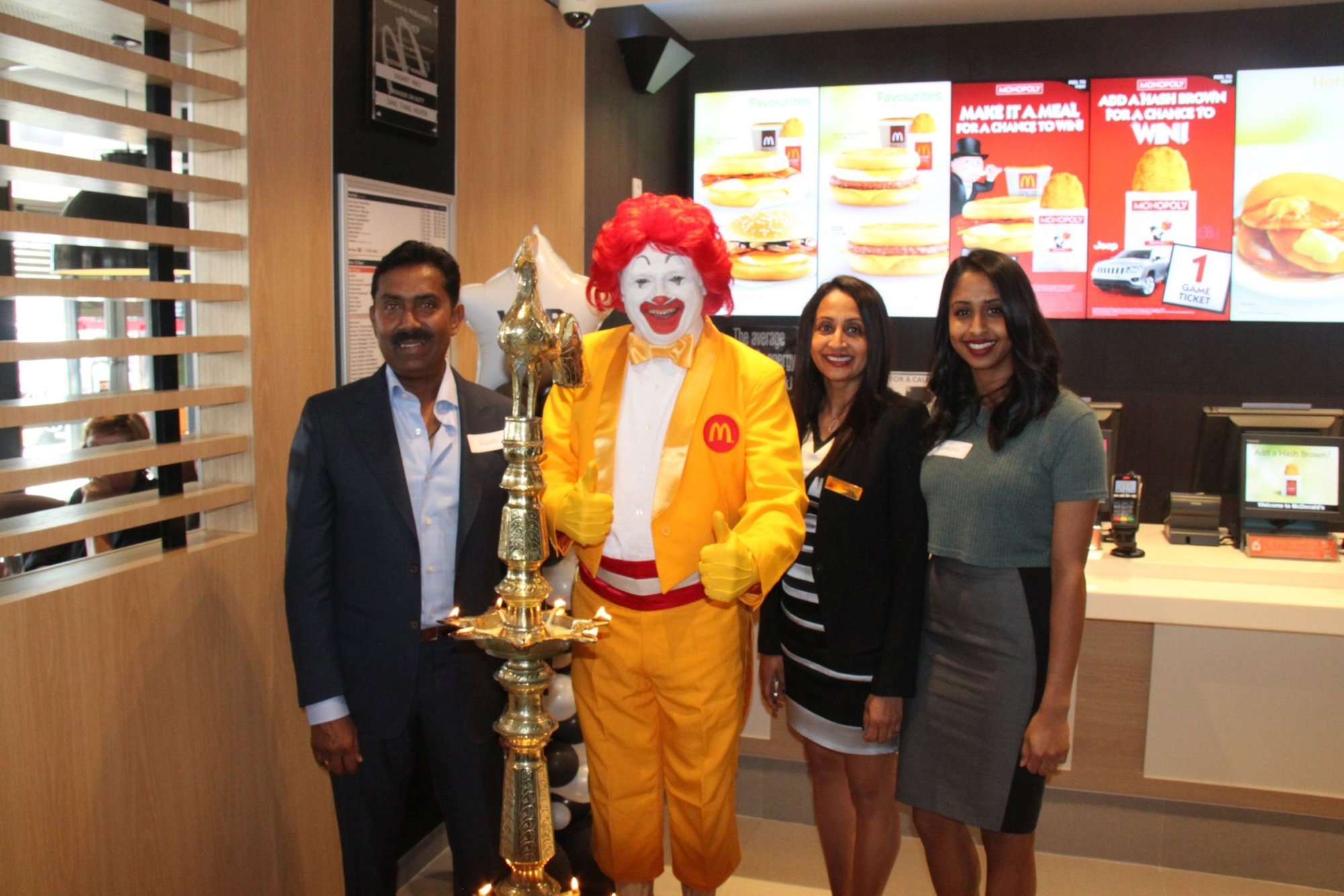 Giving back: Shanti, Arosha and Tamara Sivaraj with Ronald McDonald at the Yanchep restaurant.