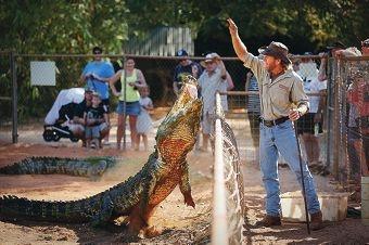 Chris Baker feeds the crocodiles at Malcolm Douglas Wilderness Park.