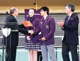 Perth Archdiocese vicar general Peter Whitely presents Irene McCormack Catholic College captains Hayley James and Thomas Tang with their plaque, as principal Robert Marshall looks on.
