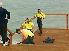 Workers remove the padlocks at the boardwalk.