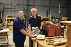 Cockburn Men's Shed secretary Ross Heseltine and Geoff Webb, from the Rotary Club of Cockburn, with a defibrillator.