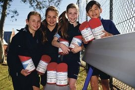 St Kieran Catholic Primary School Year 6 students, from left, Lilah Fazari, Sarah Catena, Sophia Wood and Sean Song with one of the park benches the school bought with money raised from five cent coins [NAMES OK]