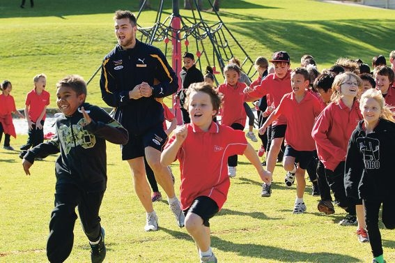 West Coast Eagle Fraser McInnes puts the students at Yale Primary School through their paces. Picture: Marcelo Palacios d424196