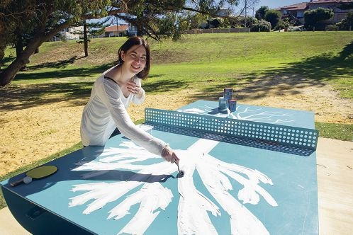 Elizabeth Marruffo is painting the public table tennis table at Geneff Park.