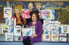 Jai Thompson, Joshua Loftus and Paige Taylor hold up packets of new pyjamas with Tina Bennett from The Spiers Centre.d423781