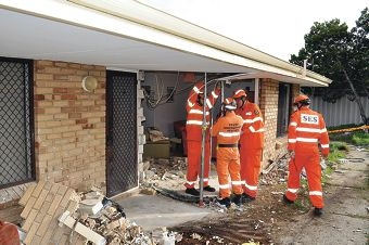 SES volunteers work to prop up the damaged home.
