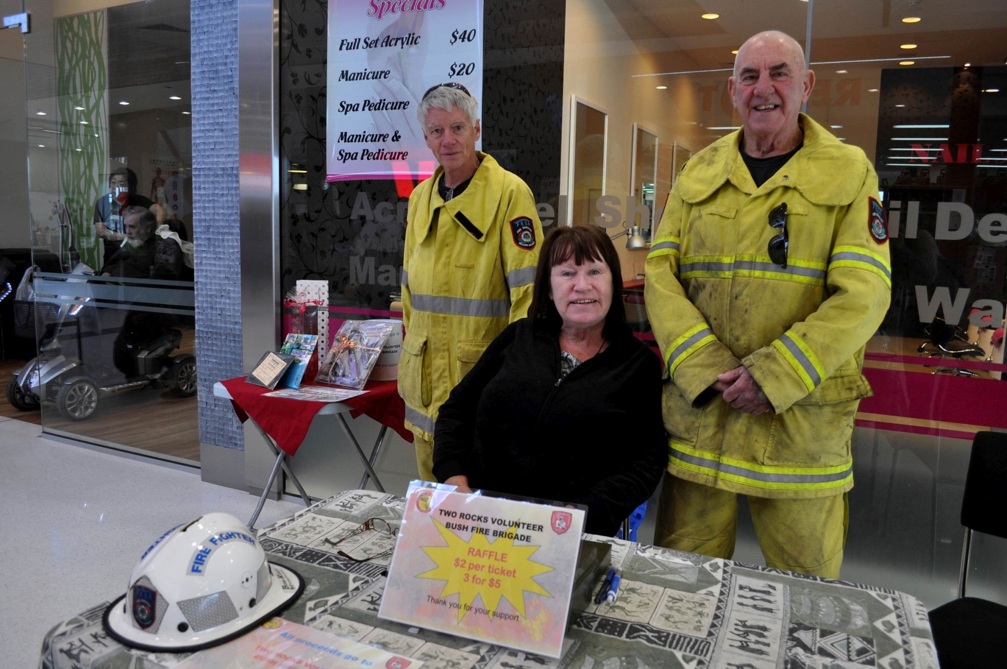 Two Rocks Volunteer Bush Fire Brigade's Derek and Moira Young with Alex Robins selling raffle tickets