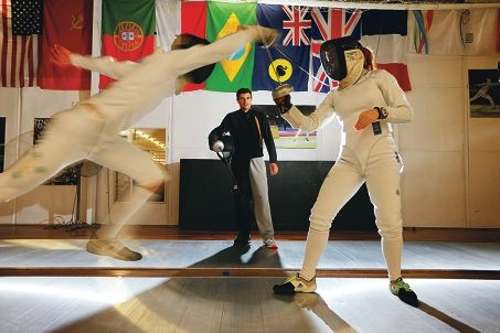 Lachlan Bunny (15), left, from Shenton College and Alanah Maclaurin (16) from PLC duel, watched by fencing state coach and head coach at UWA Tuko Maia. Picture: Andrew Ritchie www.communitypix.com.au d422150