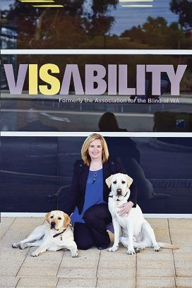 VisAbility CEO Clare Allen with guide dog puppies-in-training Goldie (left) and Zephyr outside the organisation's headquarters in East Victoria Park.
