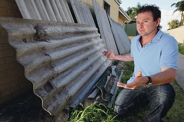 Ryan Hopkins with the section of damaged fencing. Picture: Bruce Hunt www.communitypix.com.au d421291