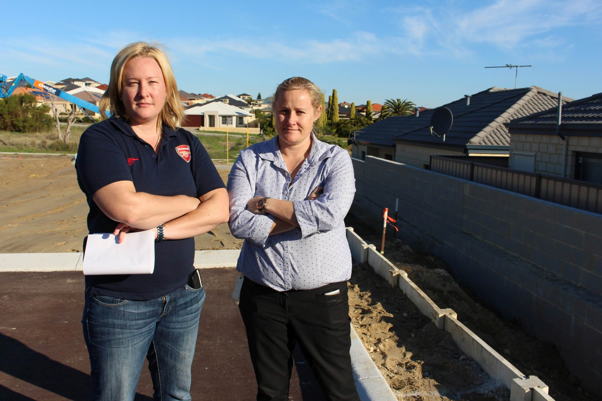 Caroline Eriksen and Lisa Beatty standing at the carpark with the wall and their properties in background.