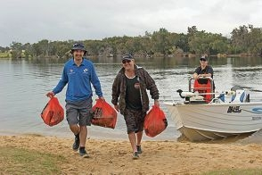 Recfishwest research officer Leyland Campbell with Lisa and Nick Davis volunteering at the Reel It In clean-up day in Bayswater.