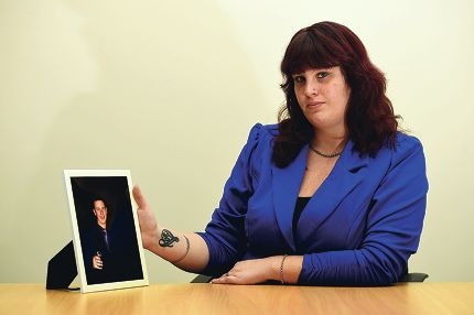 Kym Woolcott with a picture of her brother, who committed suicide.d420182