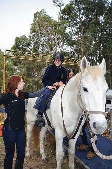 Ryan Munteanu enjoys his horse ride at Hills RDA, assisted by volunteers Kate Wilkinson and Rose Grenfell.