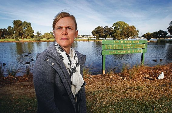 Environmental officer Julie Ophel in front of the 'feeding of birdlife is discouraged' sign at Lake Hurlingham in South Perth.