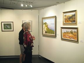 Visitors look at some of Lyn Lee's artwork.