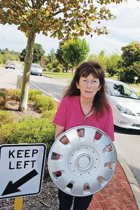 Marie Fritz, who has asked the authorities for 35 years to make Acanthus Road safer, pictured with a hub cap, which she says regularly come loose from cars as they speed around a traffic island near her house. Picture: David Baylis d418157