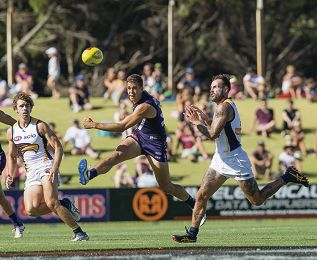 Local football star Stephen Hill gets a kick away for the Dockers. Pictures: Dan White West Coast midfielder Luke Shuey is tackled by Fremantle's Matt de Boer.