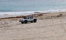 A four-wheel-drive vehicle on the beach.