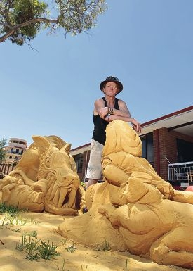 Sand sculptor Tim Darby with his work Go ahead wolf. Make my day. Picture: Martin Kennealey www.communitypix.com.au d413594