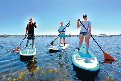 Stand-up paddling instructor Sally Simpson, centre, with students Toby Phillips and Adele Mepstead.