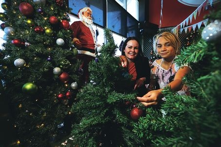 Fiona Lander of Perth Airport and Ruby Riley among Christmas decorations being donated to Princess Margaret Hospital.