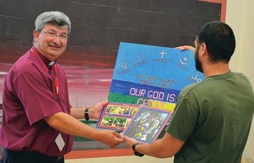 A prisoner shows Archbishop Herft some of his artwork.