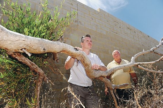 Carine residents Adam Frediani and Bruce Rintoul in front of the seven-metre high retaining wall. Picture: Marcus Whisson d411771