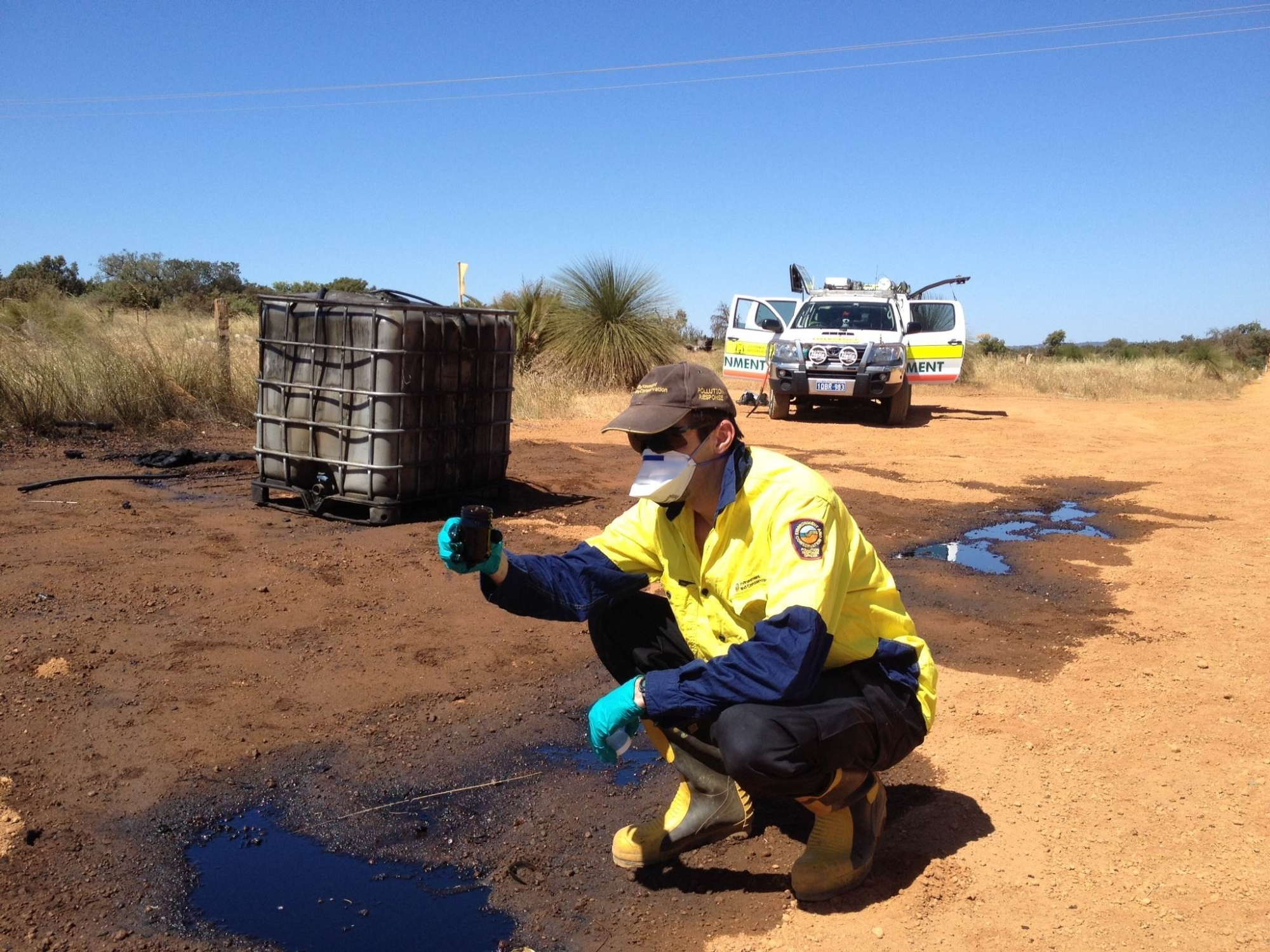 An officer from the Department of Environment Regulation investigates the illegal dumping of more than 1000 litres of used engine oil near Ellenbrook.