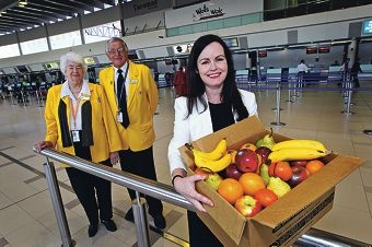 Gold coat ambassadors Roma Kilpatrick and Murray Hasse with airport executive Fiona Lander carrying a box of fruit for staff. Picture: David Baylis www.communitypix.com.au d410944
