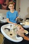 Naturopath Catherine Randabel looks on as Mel Crisp, from Hair Fusion, uses the Headbedd411141