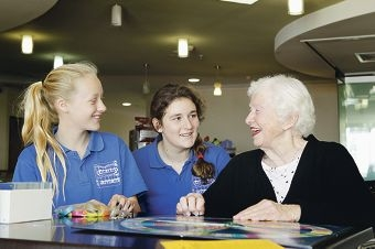 Aegis Hilton Park Aged Care resident Violet Fort shares stories with East Fremantle Primary School Year 7 students Freya Prall and Francesca Nardi.