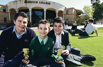 Julien Ladeira (centre) holding two of his trophies, with brothers Christoper and George.