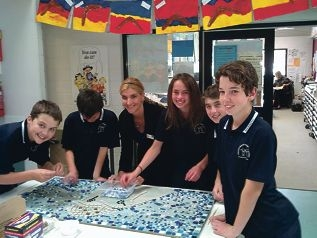 Edith Cowan University art student Holly Rutter at work on the |mosaic with Year 7 students Ethan Grant, Jake Te-Rata, Lauren Wynne, Kayden Argus and Michael Luplau.