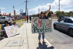 Smile Protestors captured the attention of passing motorists and pedestrians.