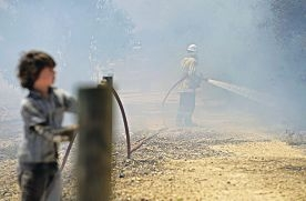 A boy watches as a firefighter battles a blaze. Picture: Elle Borgward www.communitypix.com.au d394359