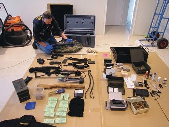 An officer inspects weapons found during raids in Sorrento and Waikiki. Picture: Australian Customs and Border Protection Service