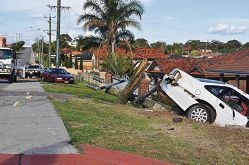 Stephen Newton and brother Jeff Vesperman with the Holden Commodore that snapped a power pole as it came frighteningly close to crashing through their home.