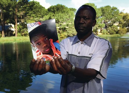 Materno Biwot holds a photograph of his son Jenon who died after drowning earlier this year off a Mindarie beach.Photographer: Matt Jelonek 406882c