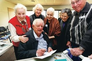 Ray Krakouer signs copies of his book on the Alkimos for residents.