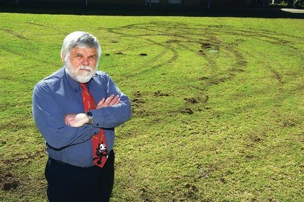 Quinns Rocks Primary School principal John Nowicki examines damage to the school lawn.