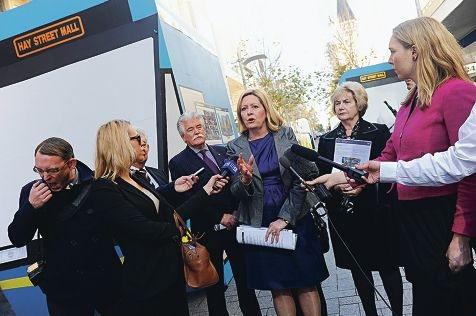City of Perth Lord Mayor Lisa Scaffidi talks to the media in Hay Street Mall with two faux light rail trains in the background.