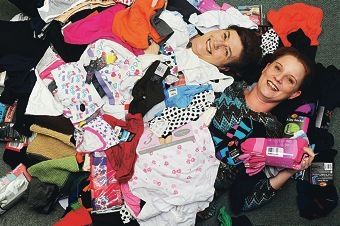 Community Newspaper Group advertising executive Margaret Cheetham and sales manager Melinda Prinsloo buried under a pile of donated socks and jocks. Picture: Marcus Whisson d405861