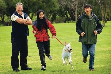 General Inspector RSPCA Trevor Prentis with Zhuofans Zhou and friend Li Ye having a good time with their dog ''Trevor''. Picture: Marcelo Palacios www.communitypix.com.au d406050