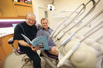 Max Trott, who has been a dentist and partner at the practice for most of his career, looks at a book celebrating the clinic's 90 years with Scott Glaskin, the founder's grandson.