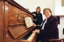 Joan King at the piano with City heritage officer Catherine Lyons-Nash looking on.